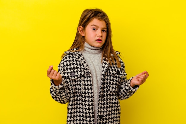 Little girl isolated on yellow wall showing that she has no money