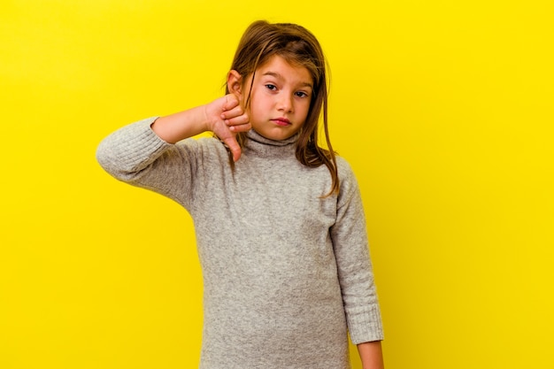 Little girl isolated on yellow wall showing thumb down, disappointment concept