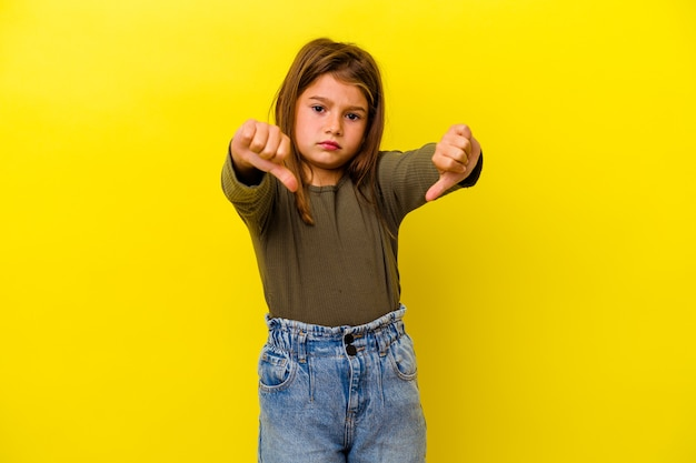 Little girl isolated on yellow wall showing thumb down