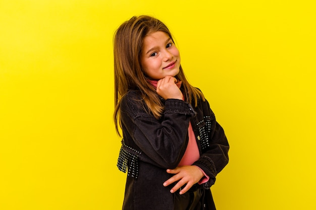 Little girl isolated on yellow wall smiling happy and confident, touching chin with hand