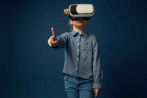 Little girl in jeans and shirt with virtual reality headset glasses isolated
