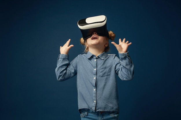 Bambina in jeans e maglietta con occhiali per cuffie per realtà virtuale