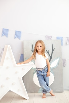 Little girl in jeans and a white t-shirt stands by the luminous star of the lamp. large decorative retro star. christmas, new year. big star with light bulbs on a concrete wall. scandinavian interior