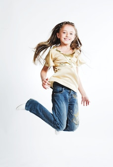 Little girl jump over white background