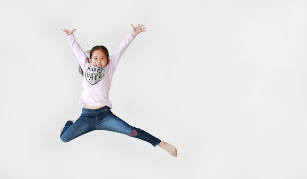Little girl jumping on air over white background
