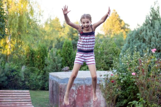 Little girl jumping on trampoline in the garden