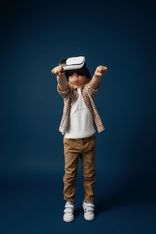 Little girl jumping with virtual reality headset glasses isolated