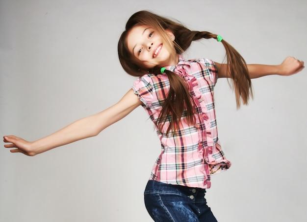 少女は灰色の壁にジャンプします