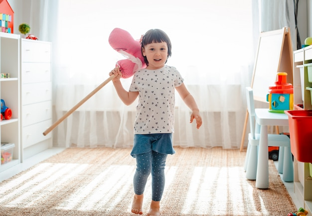 Little girl jumps and runs on  horse stick in the nursery.