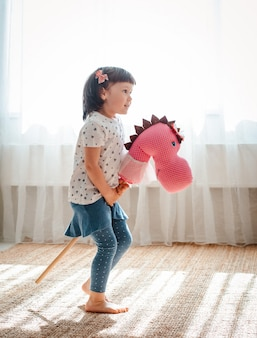 Little girl jumps and runs horse stick in the nursery.