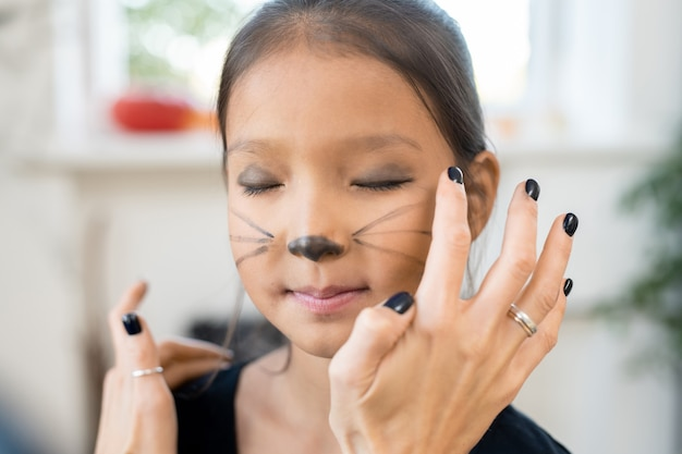 Little girl keeping eyes closed while woman applying eyeshadow on her eyelids