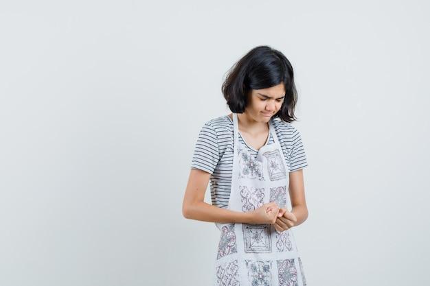 Tシャツ、エプロンで拳を握りしめ、感謝の気持ちを表す少女。