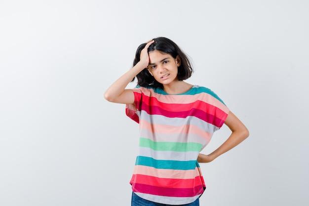 Bambina che tiene la mano sulla testa in maglietta e sembra dispiaciuta. vista frontale.