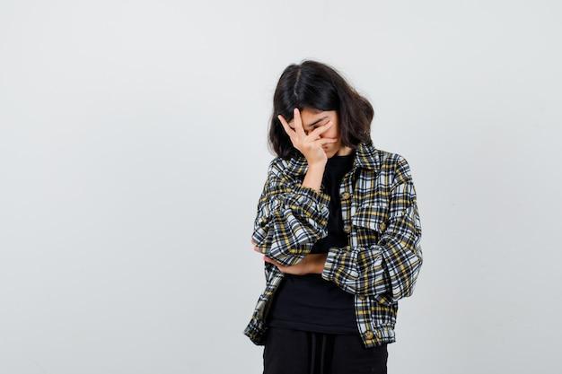 Tシャツ、ジャケットで顔に手を保ち、疲れ果てているように見える少女。正面図。