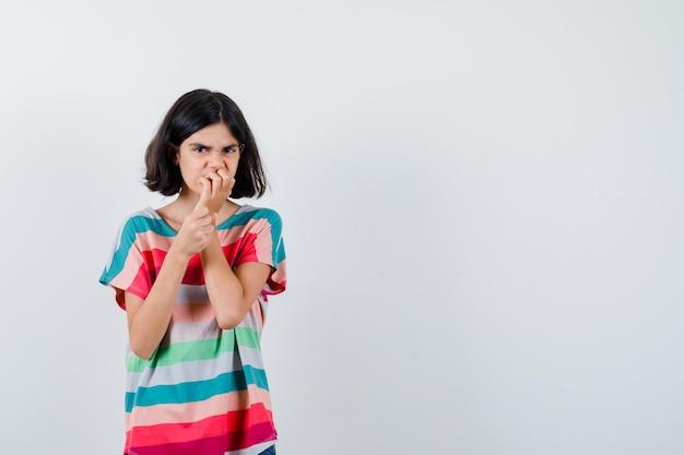 Маленькая девочка держит руку на рту в футболке и выглядит сердитой. передний план.