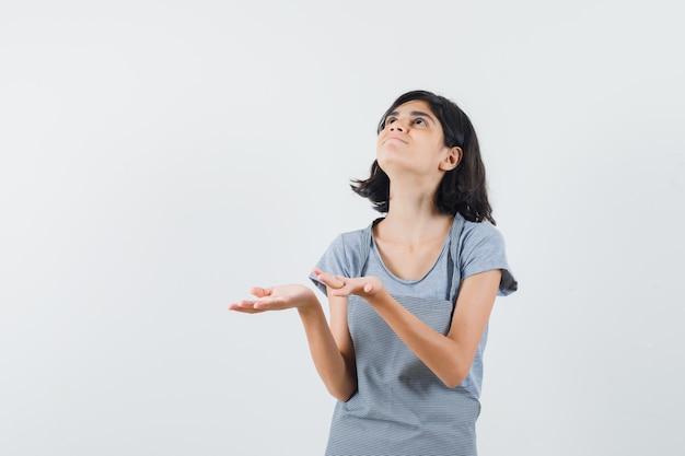 Маленькая девочка держит руки в молитвенном жесте в футболке, фартуке и выглядит благодарным. передний план.