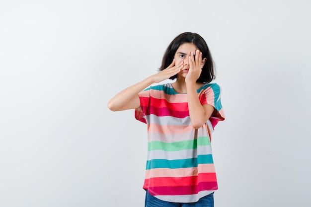 Tシャツで目と頬に手を置いて、無力な正面図を探している少女。