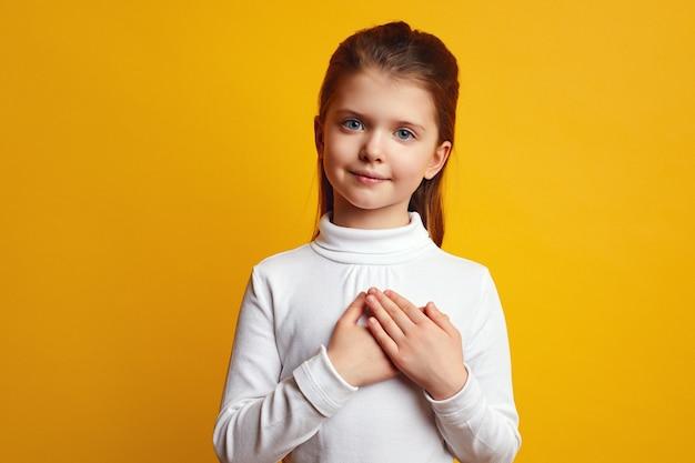 Маленькая девочка держит обе ладони на груди, изолированные на желтом фоне