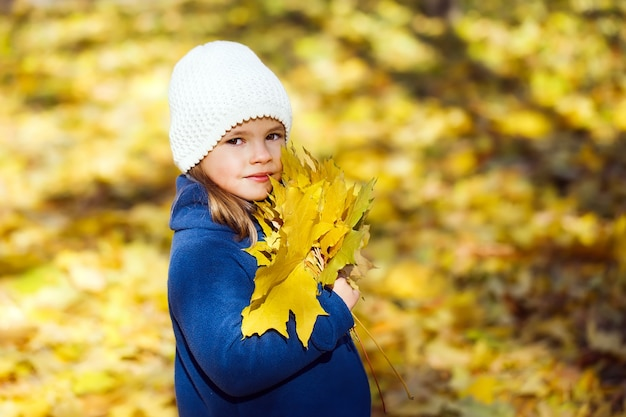 Little girl keeps leafs in hand in park in the autumn