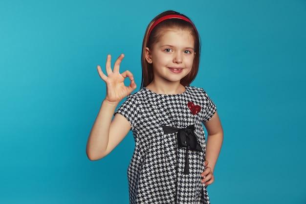 Маленькая девочка держит одну руку на талии, делает нормальный жест, любит идеальную идею