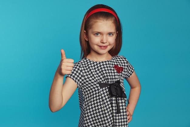 Маленькая девочка держит одну руку на талии, делает большой жест над синей стеной