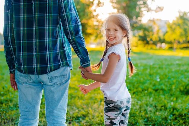 Дочь малыша маленькой девочки держа руку ее отца в природы на заходе солнца.