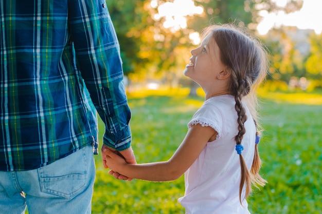 Маленькая девочка ребенок дочь держит руку своего отца в парке