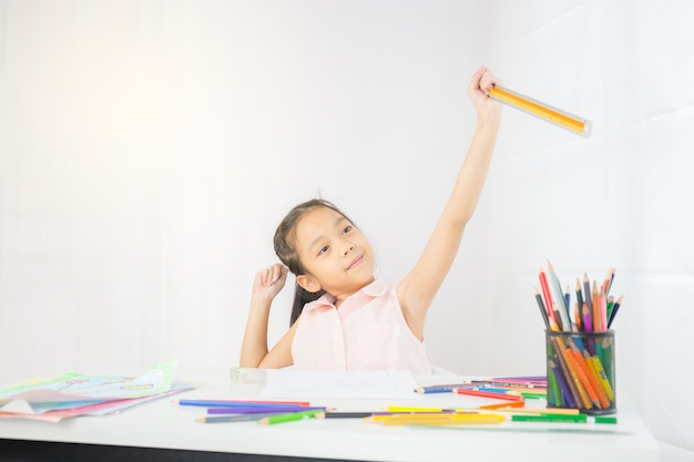 Little girl kid drawing picture with colorful pencils, ruler and pencil in hand