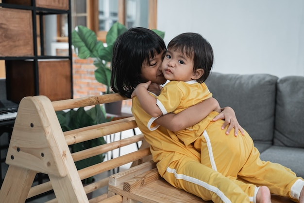 Little girl kisses her little sister while hugging sitting in the pikler triangle toys in the house