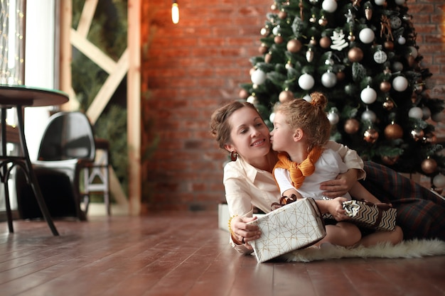 어린 소녀는 크리스마스 트리 근처에 그녀의 어머니를 키스합니다.