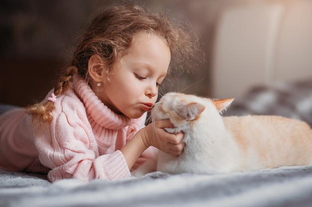 A little girl kisses her pet cat. friendship between humans and animals