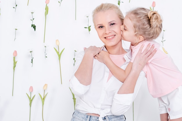 Little girl kissing beautiful mother