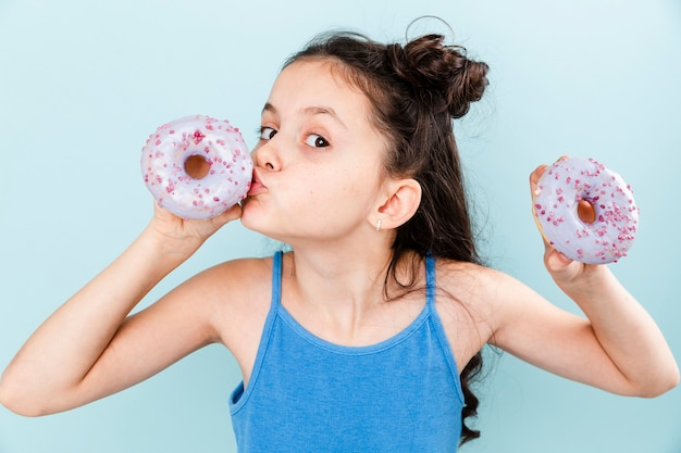 Little girl kissing delicious doughnut