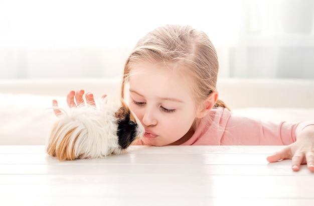 Little girl kissing guinea pig