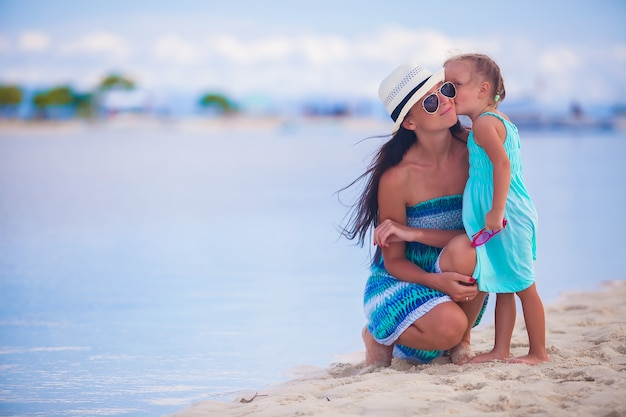Little girl kissing her beautiful mother on a white tropical beach