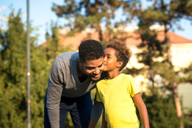 Маленькая девочка целует своего отца в парке