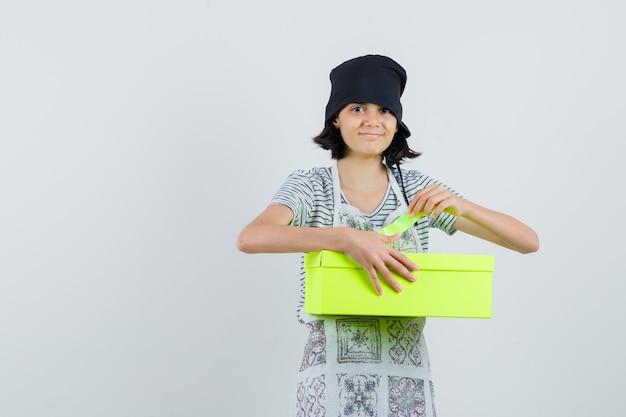 Bambina in abito da cucina che apre la scatola presente e sembra allegra,