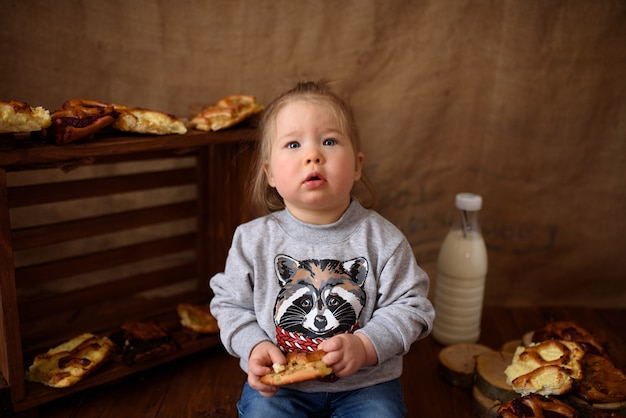 Little girl in the kitchen eats sweet pastries.