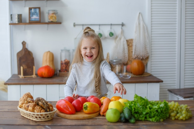 Little girl in the kitchen with vegetables smiles