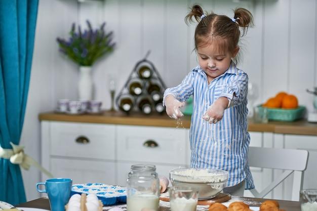 小さな女の子が自宅のキッチンで生地をこねます。彼女は愛を込めてクッキーを作ります