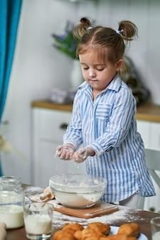 少女は自宅のキッチンで生地をこねます。