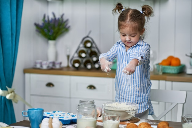 Little girl kneads dough in the kitchen at home. she cooks cookies with love