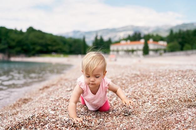 Маленькая девочка стоит на коленях на галечном пляже у воды