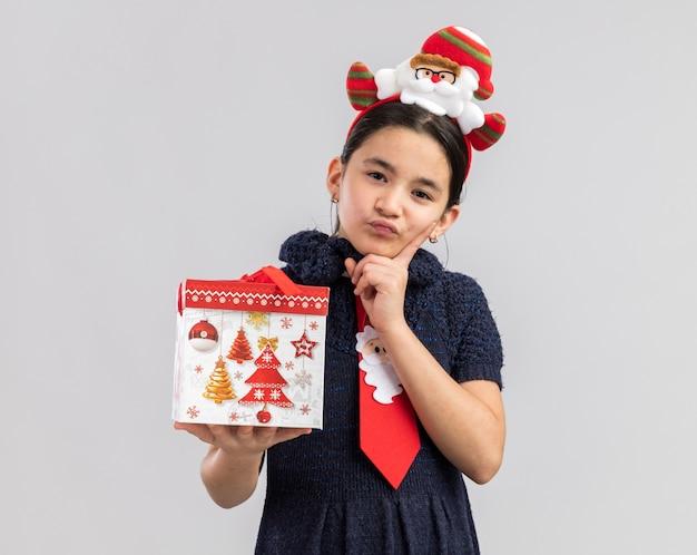 Bambina in abito in maglia che indossa cravatta rossa con bordo divertente di natale sulla testa che tiene il regalo di natale che sembra perplesso