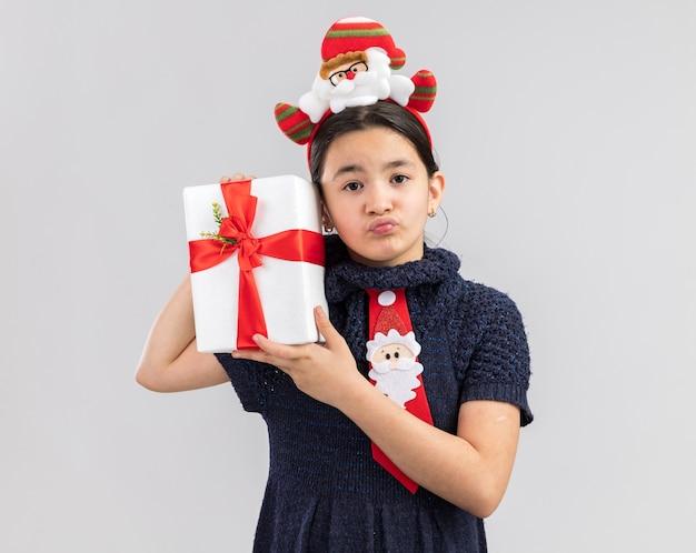 Bambina in abito in maglia che indossa cravatta rossa con bordo divertente di natale sulla testa che tiene il regalo di natale che sembra confuso con l'espressione triste