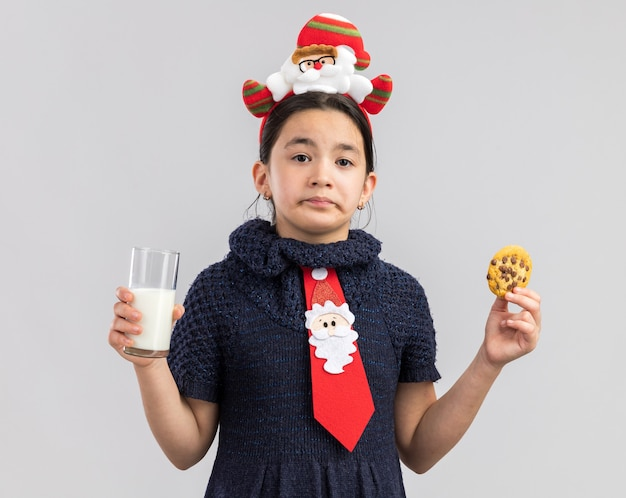 Little girl in knit dress wearing red tie with funny christmas rim on head holding glass of milk and cookie looking with sad expression
