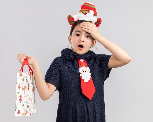 Bambina in abito in maglia che indossa cravatta rossa con bordo divertente di natale sulla testa che tiene il sacchetto di carta con il regalo di natale che sembra sorpreso e stupito