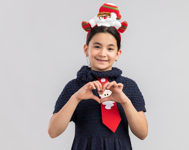 Little girl in knit dress wearing red tie with funny christmas rim on head looking smiling making heart gesture with fingers
