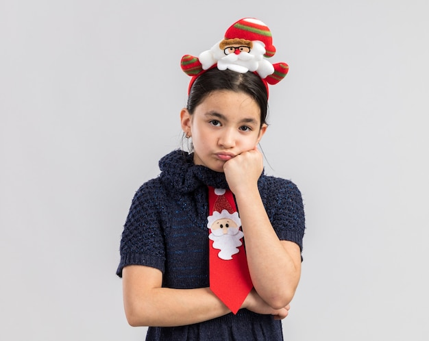 Little girl in knit dress wearing red tie with funny christmas rim on head looking tired and bored