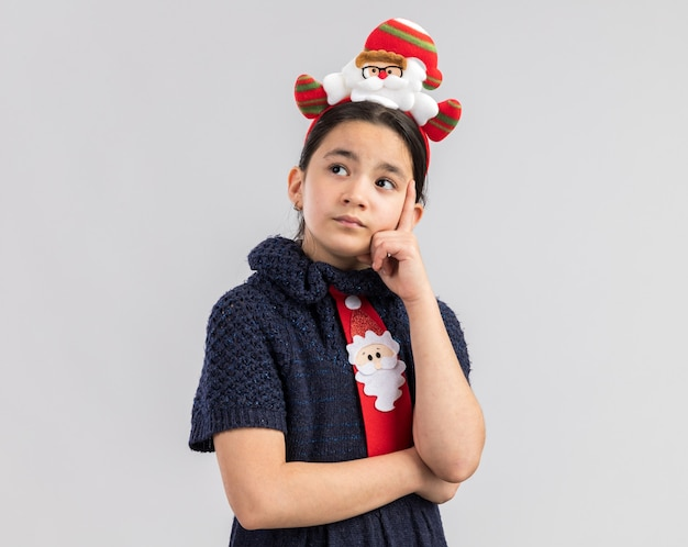 Little girl in knit dress wearing red tie with funny christmas rim on head looking up with pensive expression thinking